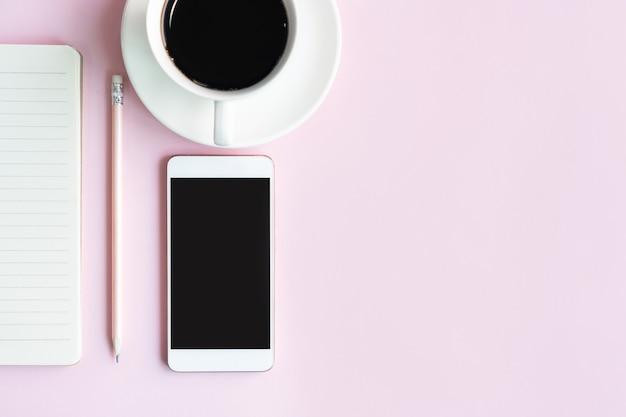 オフィスのピンクのテーブルに携帯電話、コーヒー、実業家のノートを平らに置いた。ビジネスとテクノロジーのコンセプトのトップビューとコピースペース。