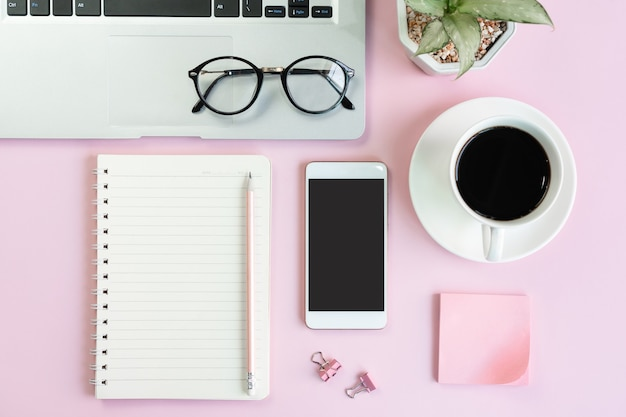 ピンクのテーブルの上に携帯電話、一杯のコーヒー、ラップトップ、学生の文房具を平らに置いた。ビジネスとテクノロジー、遠隔教育のコンセプトのトップビューとコピースペース。