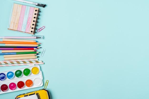 Плоская планировка современного ярко-синего офисного стола со школьными принадлежностями