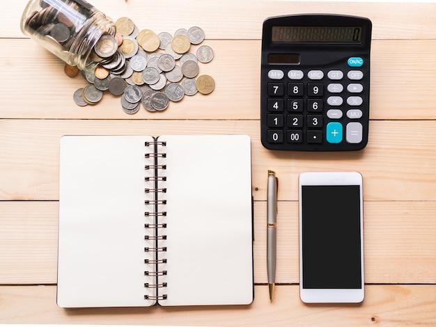 机の上のお金、スマートフォン、電卓、ノートブックのフラットレイ