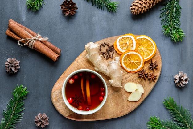 Плоская кружка горячего чая с лимоном, клюквой, гвоздикой, анисом, имбирем