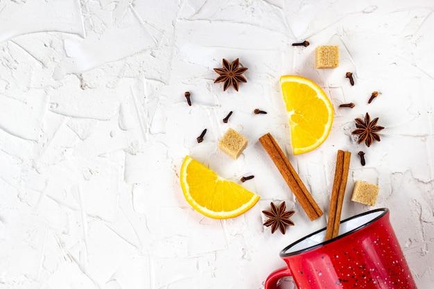 グリューワインの材料のフラットレイ。シナモン、オレンジ、カルダモン、クローブ、アニススター、白い背景の上の赤いカップ。