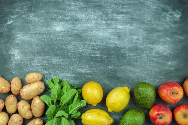 검은 배경, 음식 프레임에 여러 가지 빛깔의 생 야채를 평평하게 깔았습니다. 건강한 요리를 위한 로컬푸드. 아보카도, 감자, 레몬, 사과, 바질. 깨끗한 음식. 위에서 볼. 복사 공간