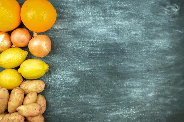 검은 배경, 음식 프레임에 여러 가지 빛깔의 생 야채를 평평하게 깔았습니다. 건강한 요리를 위한 로컬푸드. 감자, 레몬, 오렌지, 양파. 깨끗한 음식. 평면도. 왼쪽 방향. 복사 공간