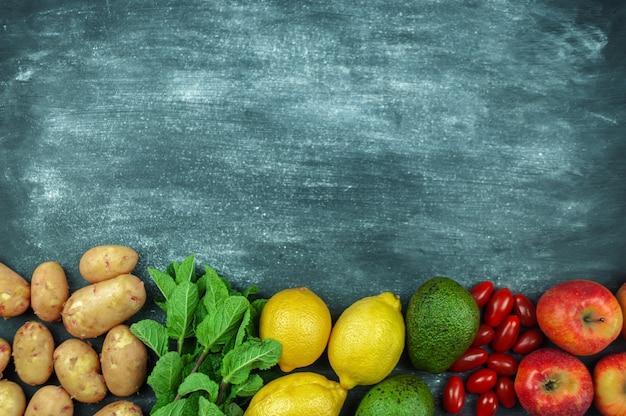 검은 배경, 음식 프레임에 다양한 색상의 생 야채가 평평하게 놓여 있습니다. 건강한 요리를 위한 현지 음식입니다. 아보카도, 감자, 레몬, 체리 토마토, 사과, 바질. 깨끗한 음식. 위에서 볼. 복사 공간