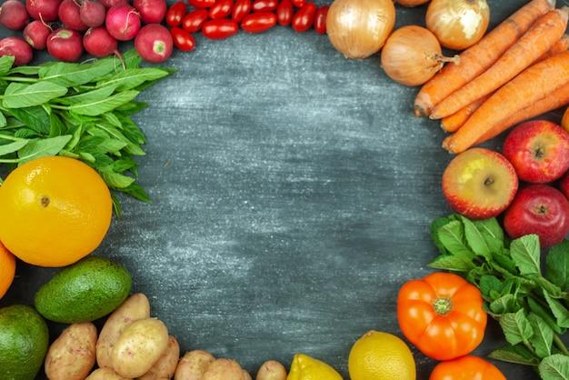 검은 배경에 여러 가지 빛깔의 생 야채를 평평하게 놓고 음식의 둥근 틀. 건강한 요리를 위한 지역 특산물. 식물을 위한 유기농 과일과 채소. 평면도. 공간을 복사합니다.