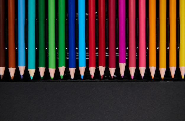 Плоская планировка разноцветных деревянных карандашей для рисования на черной поверхности