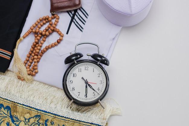 Плоская планировка мусульманской одежды и аксессуаров для намаза с четками и часами, показывающими время фаджра, молитва