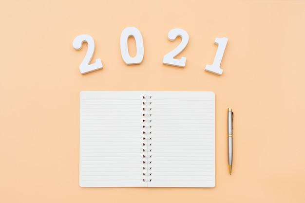 Плоская планировка ноутбука и номера на бежевом цветном фоне. концепция новогодних целей. копирование пространства.