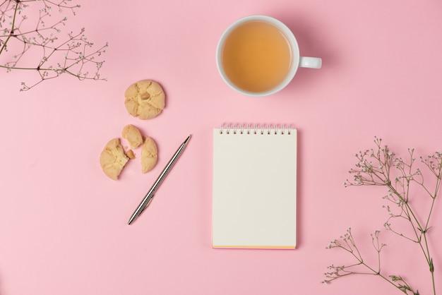 Плоский блокнот на розовом фоне с чаем и печеньем