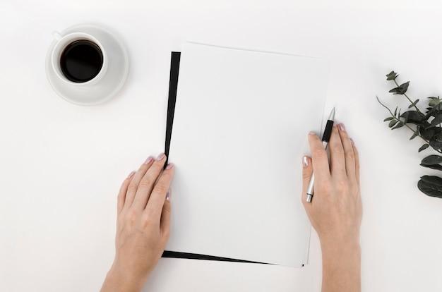 一杯のコーヒーとデスクトップ上のノートブックのフラットレイアウト