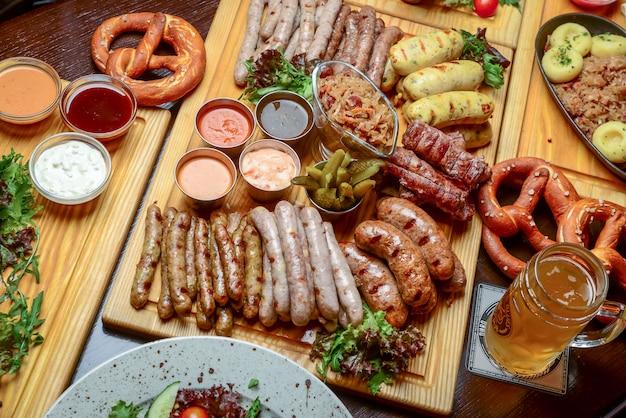 Обеденный стол октоберфест с мясными колбасками на гриле, крендельками, картофелем, огуречным салатом, соусами, пивом