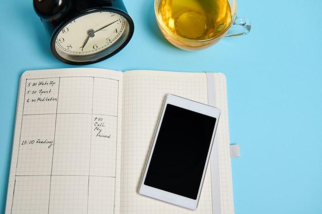 일정, 스마트폰, 차 한 잔, 검은색 알람 시계가 있는 평평한 열린 노트북이 파란색 표면에 놓여 있습니다. 텍스트 복사 공간이 있는 배경색입니다. 시간 관리, 마감일, 일정 개념