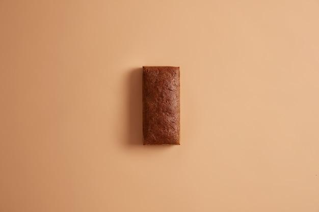 유기농 밀가루로 만든 직사각형 모양의 신선한 유기농 다크 호밀 빵을 평평하게 놓습니다. 베이지 색 바탕에 영양소 multigrain 제품입니다. 소비 할 준비가 된 전체 덩어리. 베이커리 선택.