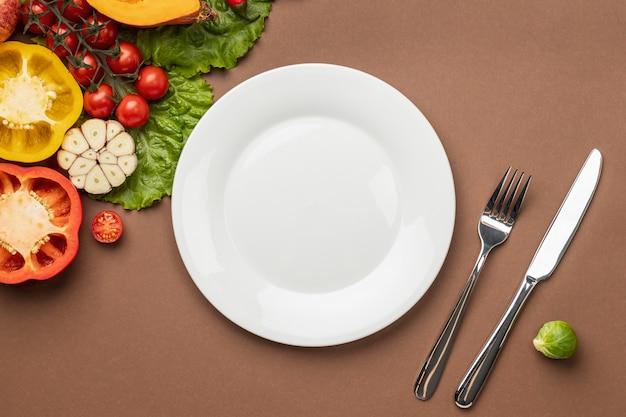 Плоская кладка органических овощей с тарелкой и столовыми приборами