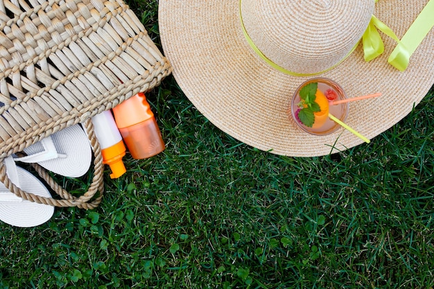 야외 밝은 여름 휴가 또는 여행 라이프 스타일 개념의 플랫 누워 밀짚 가방, 모자, 플립 플롭, 레모네이드 및 잔디 배경, 평면도, 복사 공간에 자외선 차단제 스프레이.