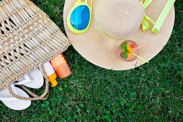 야외 밝은 여름 휴가 또는 여행 라이프 스타일 개념의 플랫 누워 밀짚 가방, 모자, 플립 플롭, 레모네이드, 잔디 배경, 평면도, 복사 공간에 선글라스와 자외선 차단제 스프레이.
