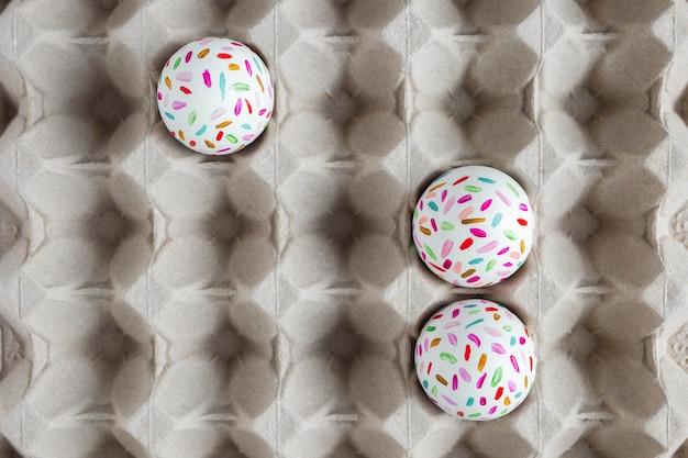 Плоские раскрашенные пасхальные яйца в картонной коробке