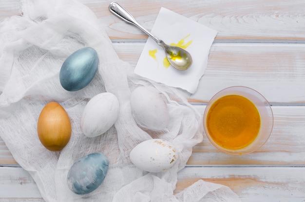 イースターの染料とスプーンで塗られた卵のフラットレイアウト