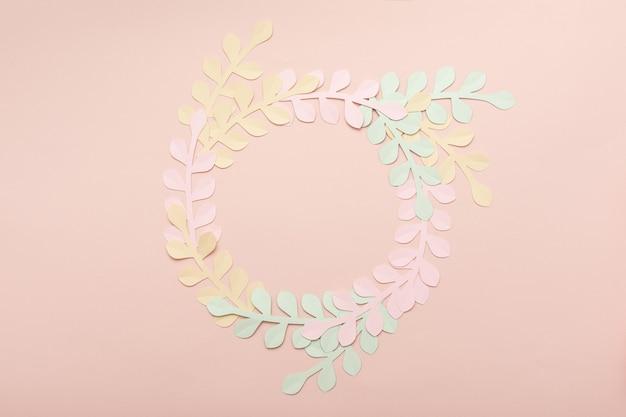 파스텔 핑크 배경에 평평한 종이 잎. 여름 패션과 트렌디한 프레임
