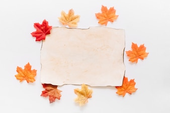 Flat lay of paper sheet with autumn leaves around