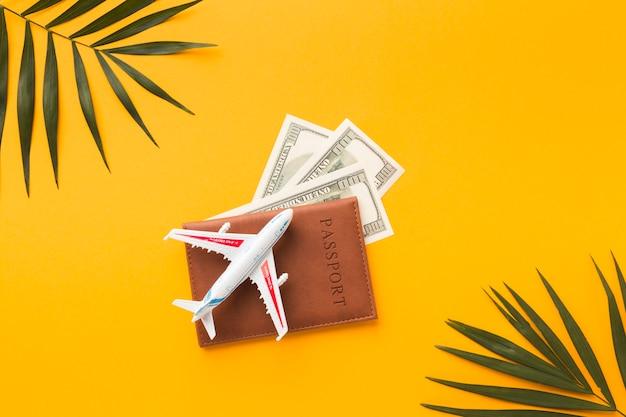 上にパスポートとお金と飛行機の置物のフラットレイアウト