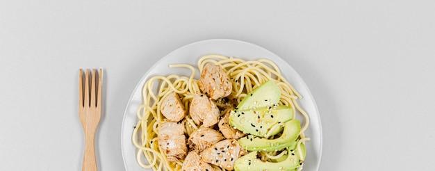 Плоская паста с мясом и авокадо на тарелке