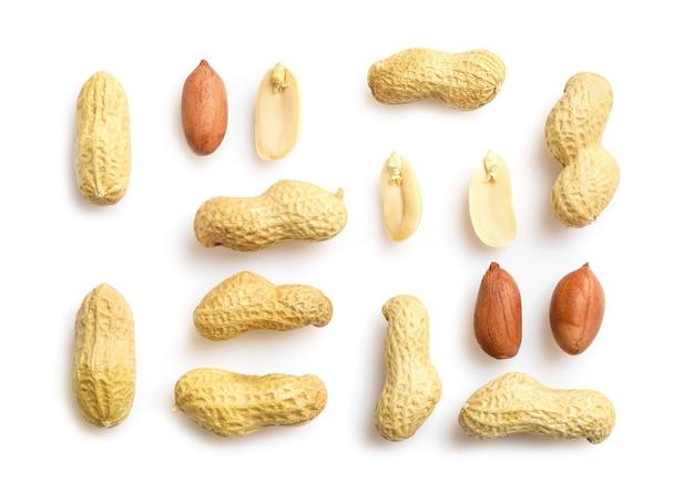 Плоская кладка арахиса в ореховой скорлупе, неочищенного и очищенного арахиса, изолированного на белом
