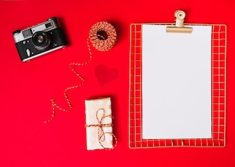 Flat lay of photo camera and blank paper