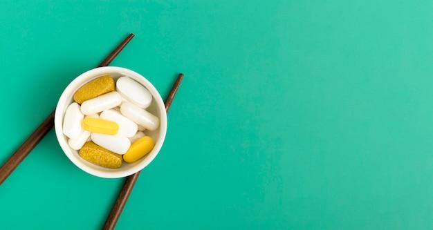 Плоская кладка таблеток в миску с палочками для еды и копией пространства