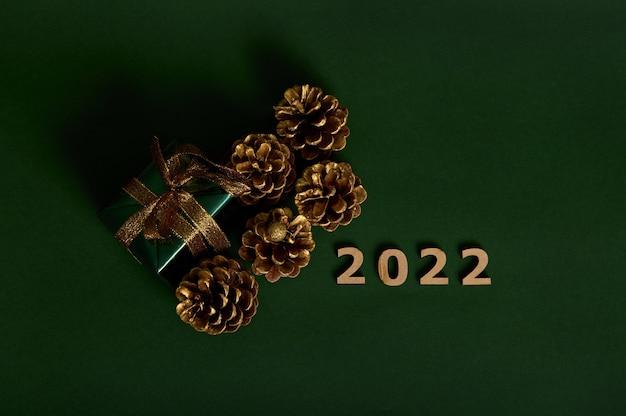Плоская планировка сосновых шишек, украшенных золотыми елочными шарами, роскошный подарок в блестящей оберточной подарочной бумаге с золотым бантом, деревянные цифры 2022 на темном фоне с копией пространства для новогодней рекламы
