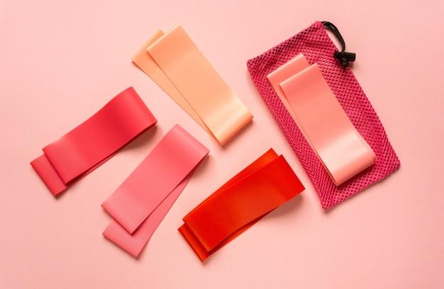Плоская планировка розовых фитнес-лент на цветном фоне, вид сверху.
