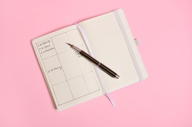 일기에 표시된 시간에 따라 플래너 템플릿과 하루 일정이 평평하게 놓여 있고 열린 노트북에 잉크 펜이 놓여 있습니다. 비즈니스 책 일기, 사무실 주최자 계획. 복사 공간