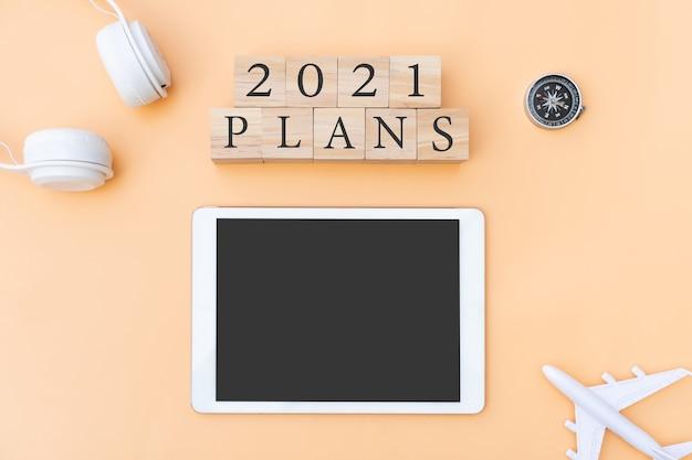ベージュの背景に平面ヘッドフォンコンパスとタブレットを備えた木製の立方体に計画の手紙のフラットレイ新年の計画と旅行のコンセプトコピースペース上面図