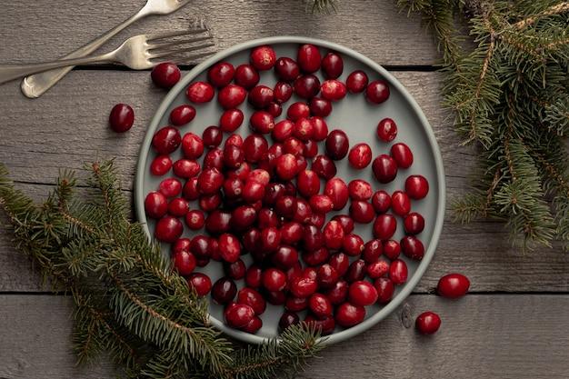 Плоская кладка тарелки из клюквы с сосной и вилками
