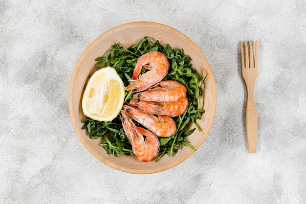 Плоская тарелка с креветками на салате с лимоном