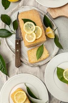 Плоское расположение тарелок с ломтиком лимонного торта и листьями