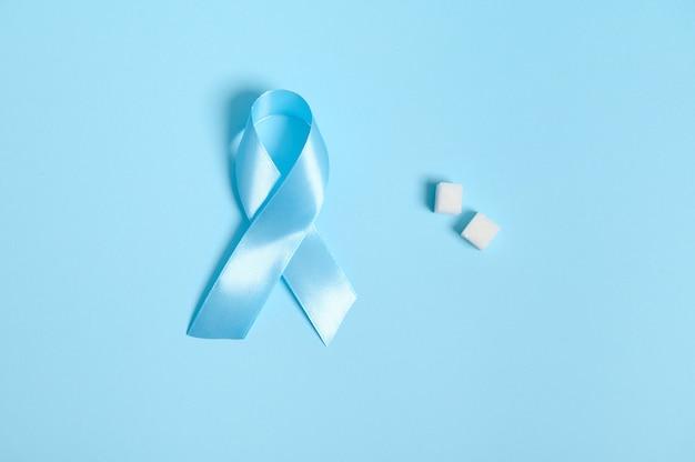 11月14日の世界糖尿病デーの象徴である、純粋に洗練された白い砂糖の立方体と青いサテンのリボンの平らな敷設。色付きの青い背景の上に分離され、医療広告用のスペースをコピーします。