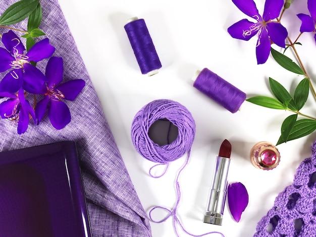 白いテーブルトップに紫色の綿の毛糸、花、ニットクロス、ラップトップのフラットレイ