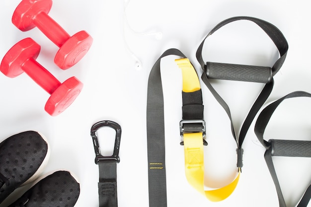 白い背景に赤いダンベル、黒のスニーカー、スポーツ用品のフラットなレイアウト。スポーツウェア、スポーツアクセサリー、トップビュー
