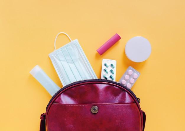 化粧品、アクセサリー、黄色のアルコールゲル消毒剤とマスクで開いた赤い革の女性のバッグのフラットレイアウト