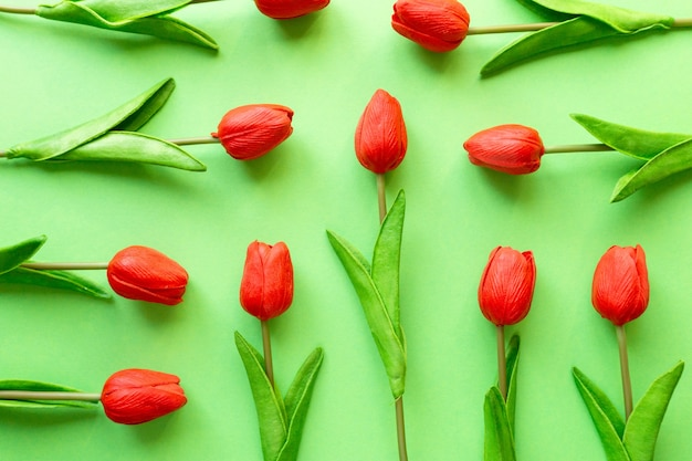 緑の背景、上面図に赤いチューリップのフラットレイ。
