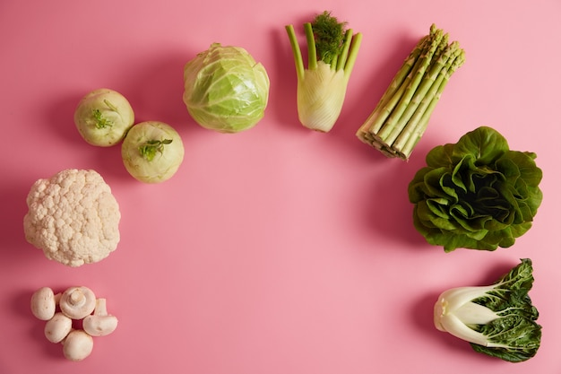 多くのビタミンと栄養素を含む熟した緑の葉野菜の平らな産卵。きのこ、ブロッコリー、フェンネル、アスパラガス、チンゲン菜を半円形に並べました。有機食品、健康的な食事の概念。