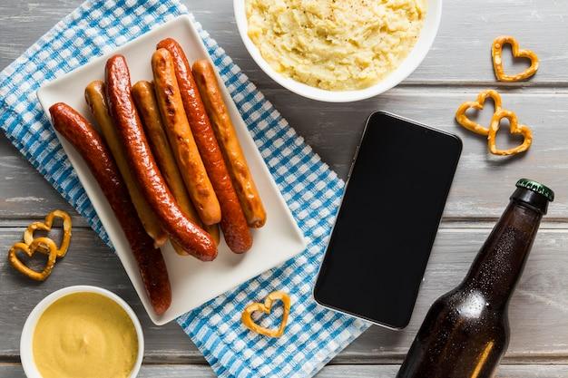 ビール瓶とスマートフォンでソーセージのフラットレイ