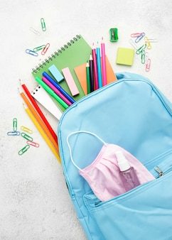 Плоская планировка школьных принадлежностей с рюкзаком и медицинской маской