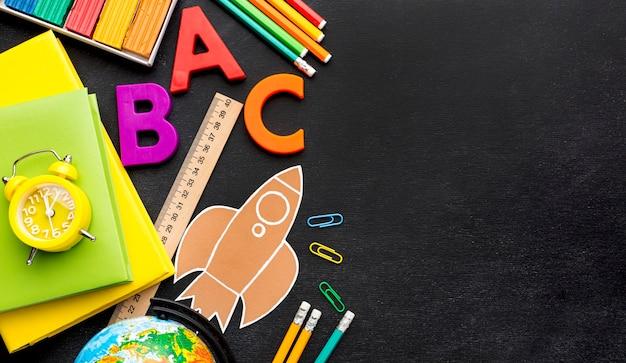 Плоская планировка школьных принадлежностей с книгами и копией пространства