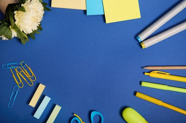 Плоская планировка школьных принадлежностей в желтых тонах, изолированных на синем фоне, копией пространства. цветы астры и канцелярские принадлежности разбросаны по кругу. вернуться к школьной концепции