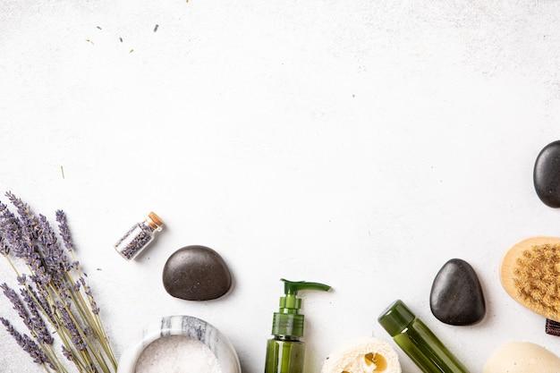 중성 색조 배경에 자기 관리 루틴이 평평하게 놓여 있습니다. 건강한 라이프스타일을 위한 라벤더 꽃과 에센셜 오일이 함유된 천연 화장품. 평면도