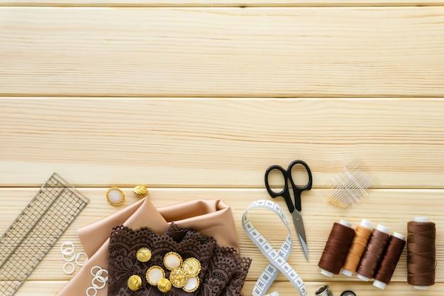 재봉 액세서리의 플랫 누워. 천, 스레드 및 나무 배경, 텍스트를위한 공간에 맞춤 도구.