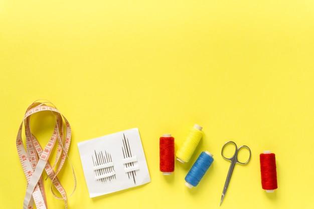재봉 액세서리의 플랫 누워. 노란색 표면에 실, 바늘, 센티미터 및 가위, 텍스트를위한 공간.